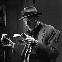 William Burroughs reading with a vodka & coke in hand