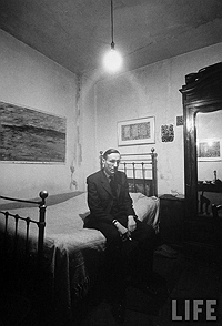 William S. Burroughs sitting on the bed of his room at the Beat Hotel, Paris, 1959, photograph by Loomis Dean